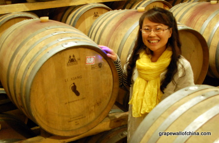 Wine maker Zhang Jing with a barrel to